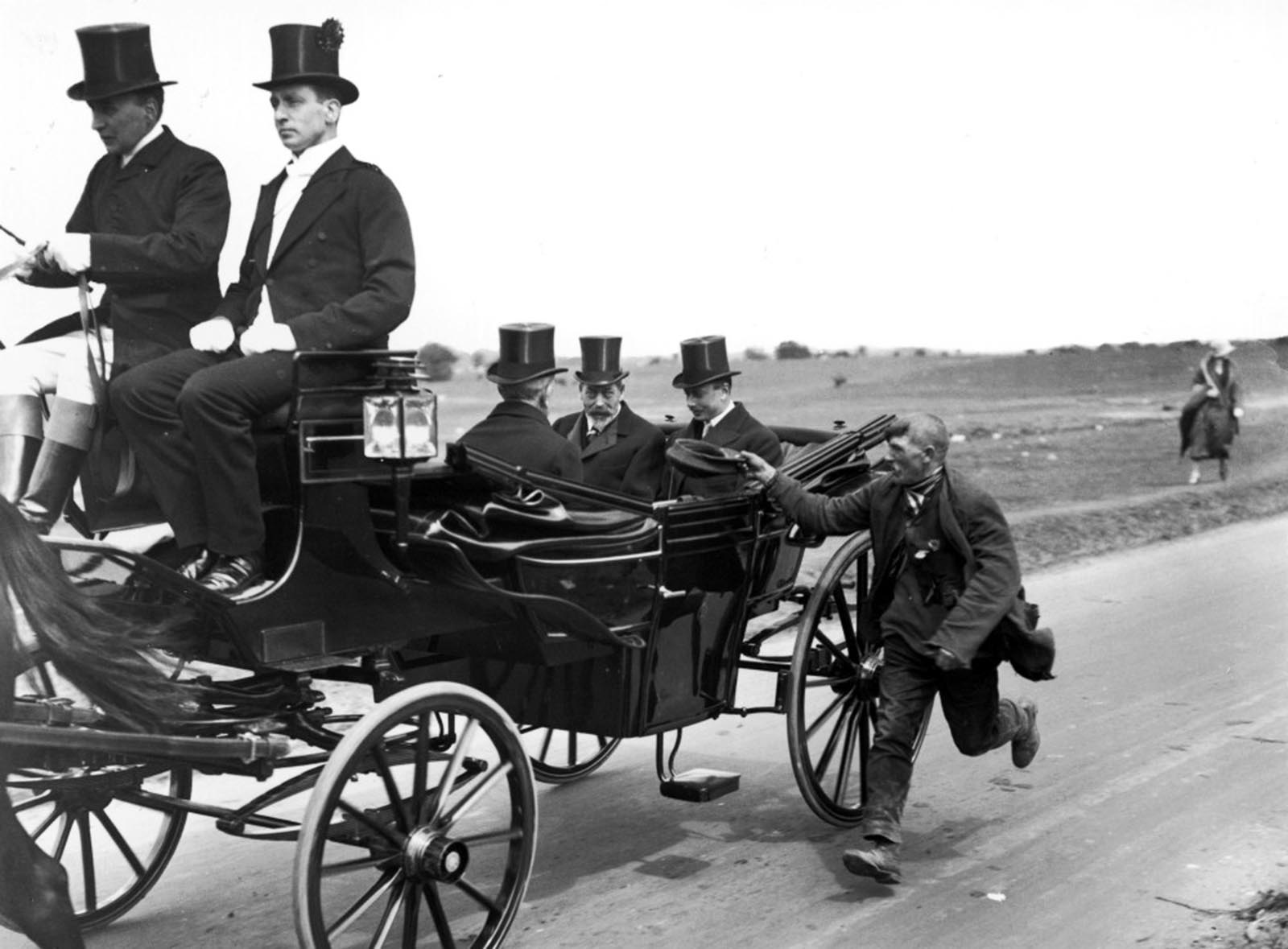 King George V. Photograph, taken in the early 1920's showing a beggar solicing money form the royal party as he runs alongside their carriage. The occupants look embarrassed.