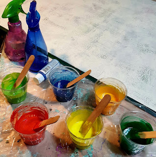 multi colored paints in cups with stirs.
