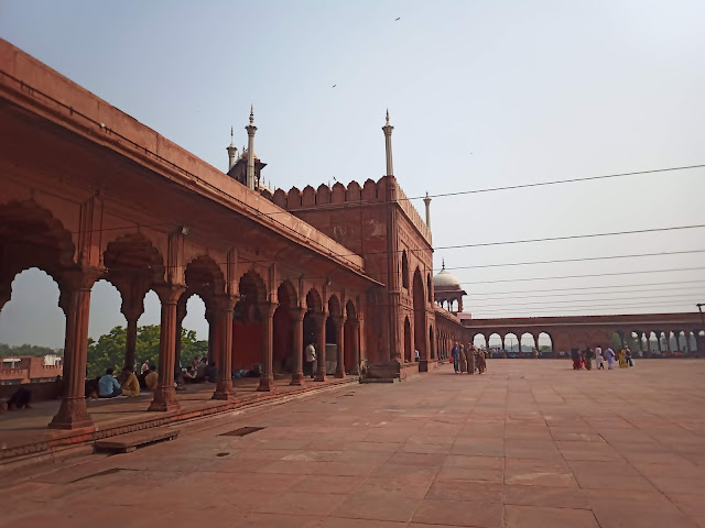 Red sandstone courtyard and exterior awning of Jama Masjid with visitors sitting underneath