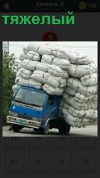 едет машины у которой в кузове тяжелый груз из мешков