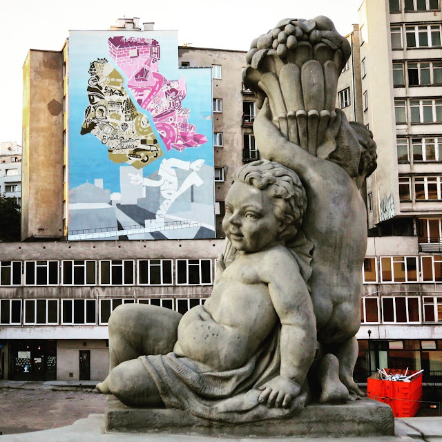 Cherub statue and street art in Warsaw, Poland