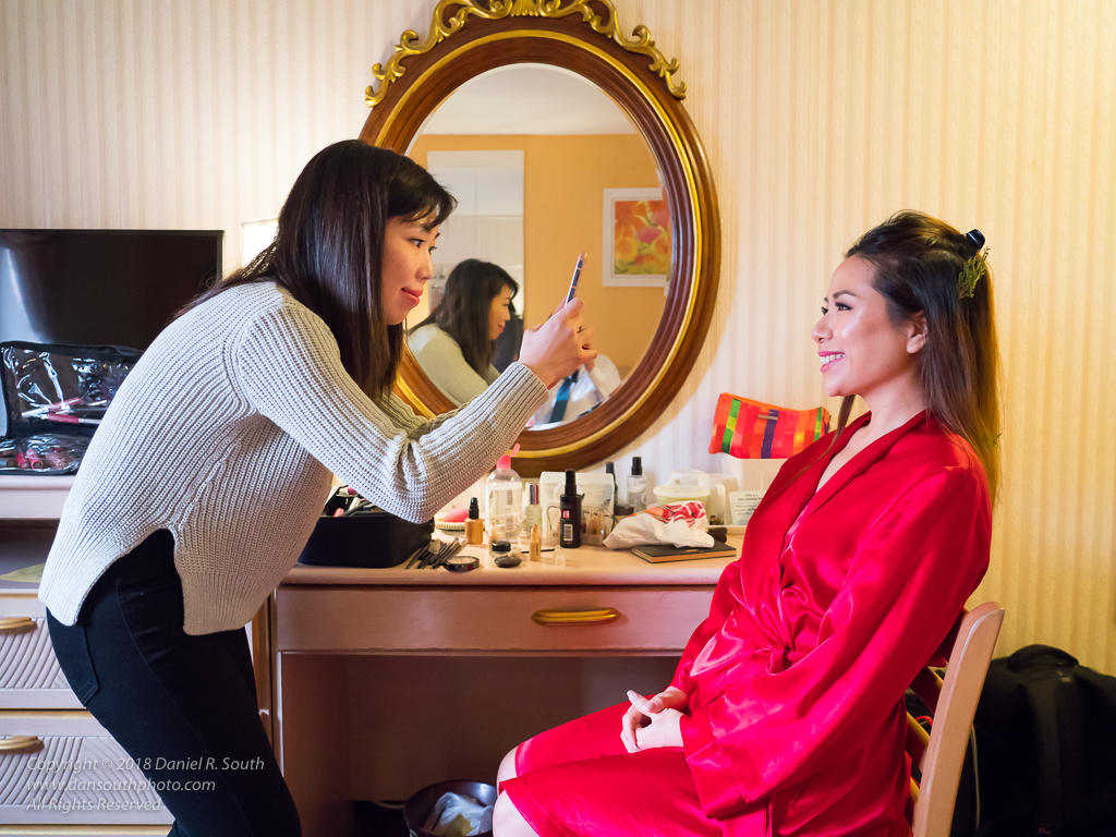 a photo of a makeup artist taking a photo of a bride with makeup applied