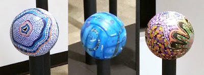 A closer view of the bottom three volleyballs. Left: dot paintings in whites, blues and pastels; centre: sea blues and greens; right: dot paintings inclue a hand outined in greens and abstract dots and colours in pinks, purples, oranges etc.