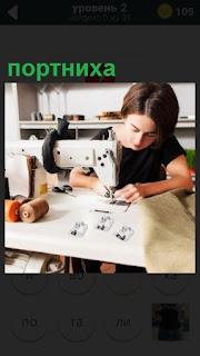 За столом около швейной машинки сидит портниха и шьет одежду