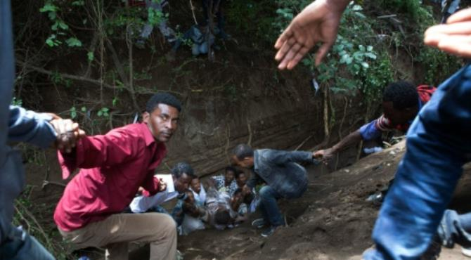 """People extract an injured man from a ditch after a deadly stampede in Bishoftu on October 2, 2016. By Zacharias Abubeker (AFP). Bishoftu (Ethiopia) (AFP) - Fifty-two people died on Sunday at a religious festival in Ethiopia to celebrate the end of the rainy season after police fired tear gas at protesters triggering a stampede.  Violence broke out at the gathering in the town of Bishoftu near the capital Addis Ababa due to the actions of """"irresponsible forces"""", the regional government said in a statement, adding that """"as a consequence, 52 people died in this crush.""""  Opposition groups had said they believed more than 100 people had been killed in the chaos after thousands of people gathered at a sacred lake for the Irreecha (thanksgiving) ceremony, in which the Oromo community marks the end of the wet weather.  Ethiopia is facing its biggest anti-government unrest in a decade and some festival participants had crossed their wrists above their heads, a gesture that has become a symbol of protest by the Oromo community, according to an AFP photographer at the scene."""