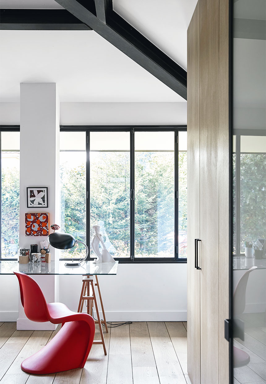 red pantone chair and glass writing desk inside of a large villa