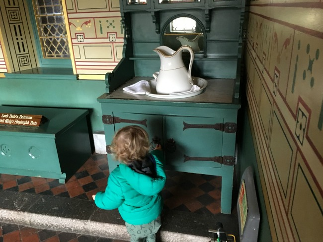 toddler opening green cupboard with jug and bowl on top