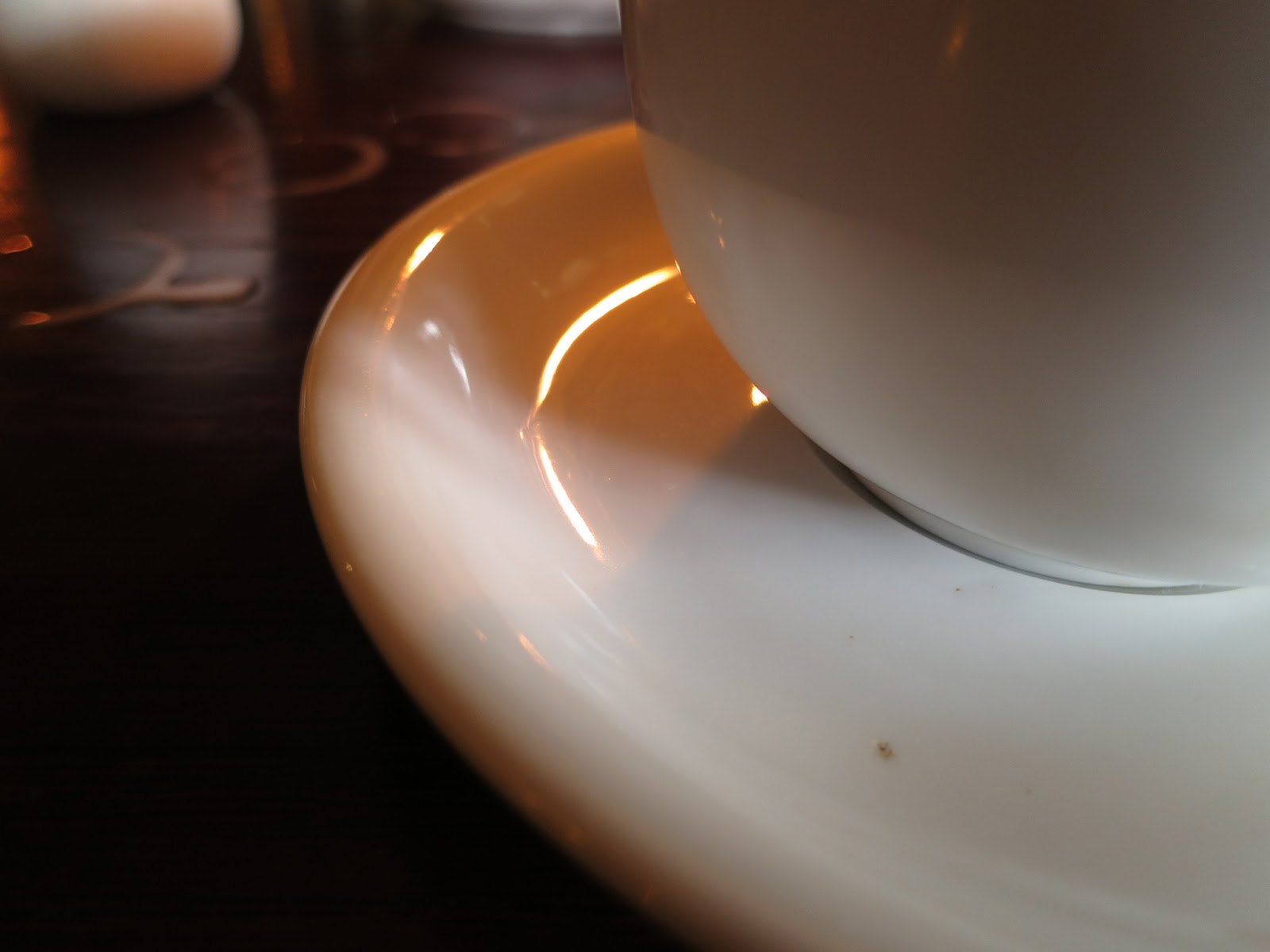 Part of coffee cup and saucer and rings on table in gloom of pub