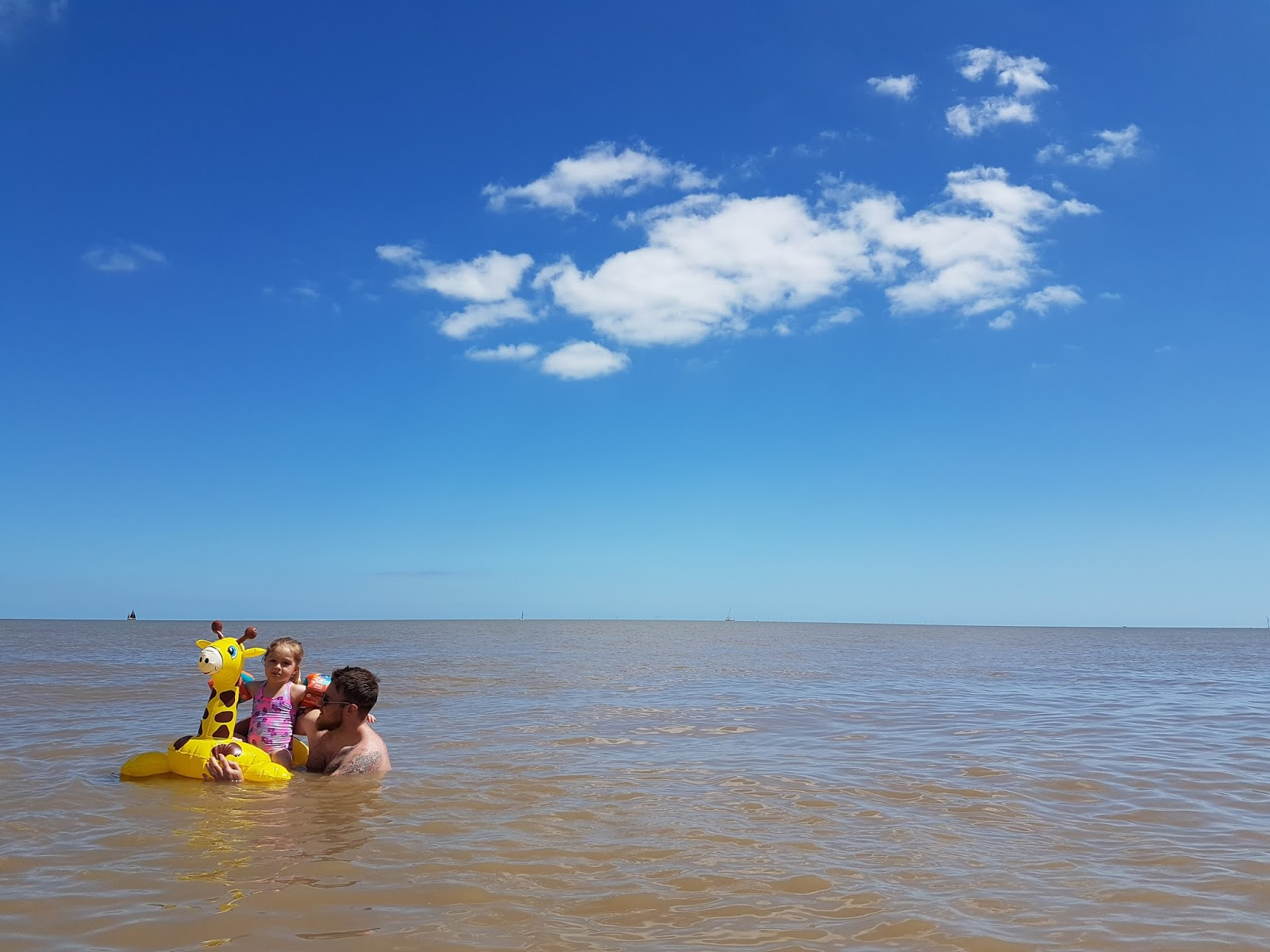 dad and daughter in the sea with giraffe float