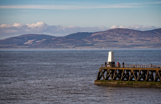Photo of Maryport lighthouse with the Scottish hills on the other side of the Solway Firth
