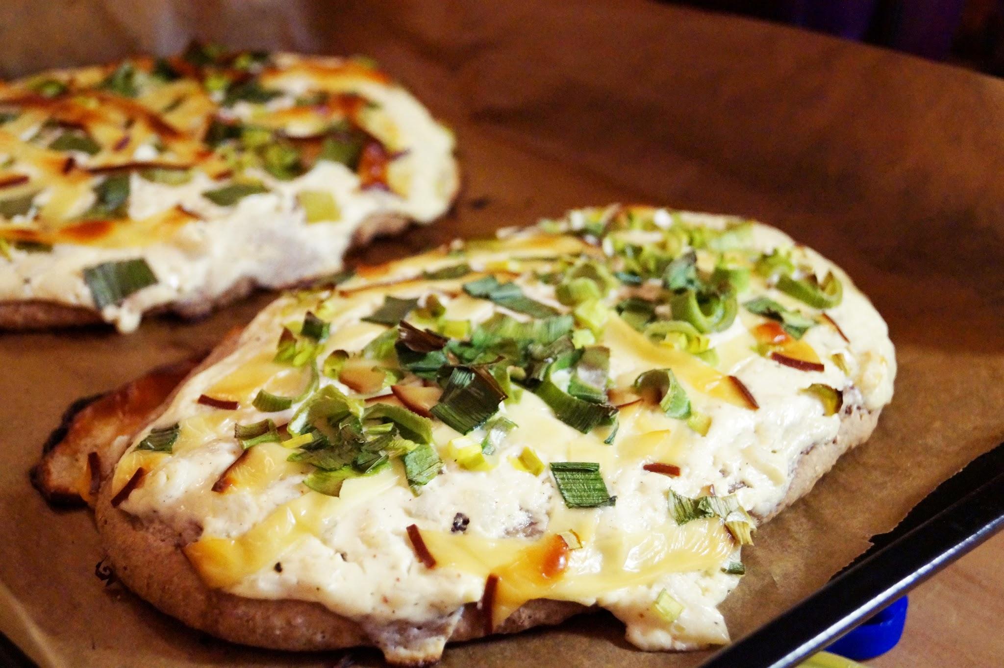 Vollkornbrot belegt mit Frühlingszwiebeln auf Sahne-Soße und mit Käse überbacken