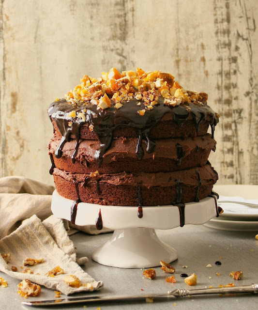 A triple layer vegan chocolate cake with nut brittle.