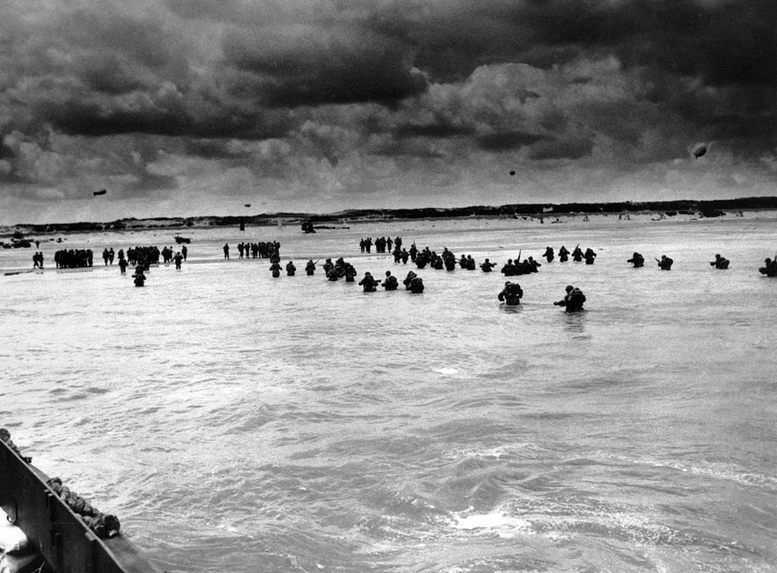 U.S. reinforcements wade through the surf as they land at Normandy in the days following the Allies' June 1944 D-Day invasion of France.