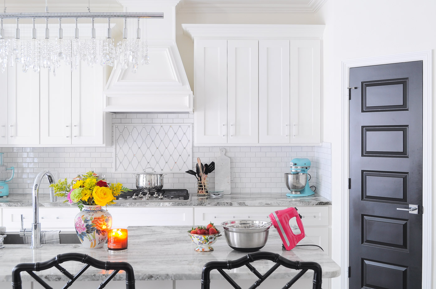 Bright white kitchen with crystal chandeliers and shaker cabinets. Love the pops of color!