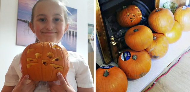 My youngest with the pumpkin she carved at school & more pumpkins for us to carve