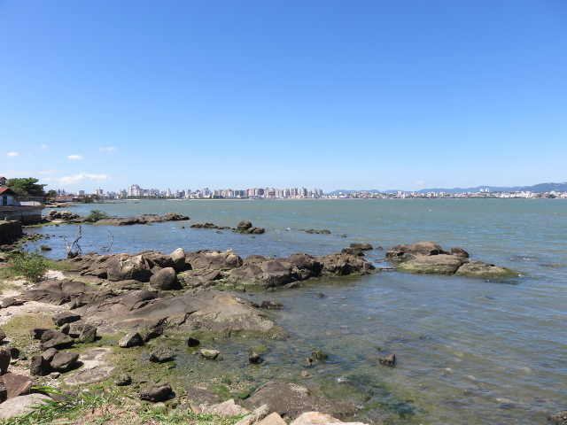 A view of the ocean from where is also possible to see some buildings on the back, those buildings are Florianópolis.