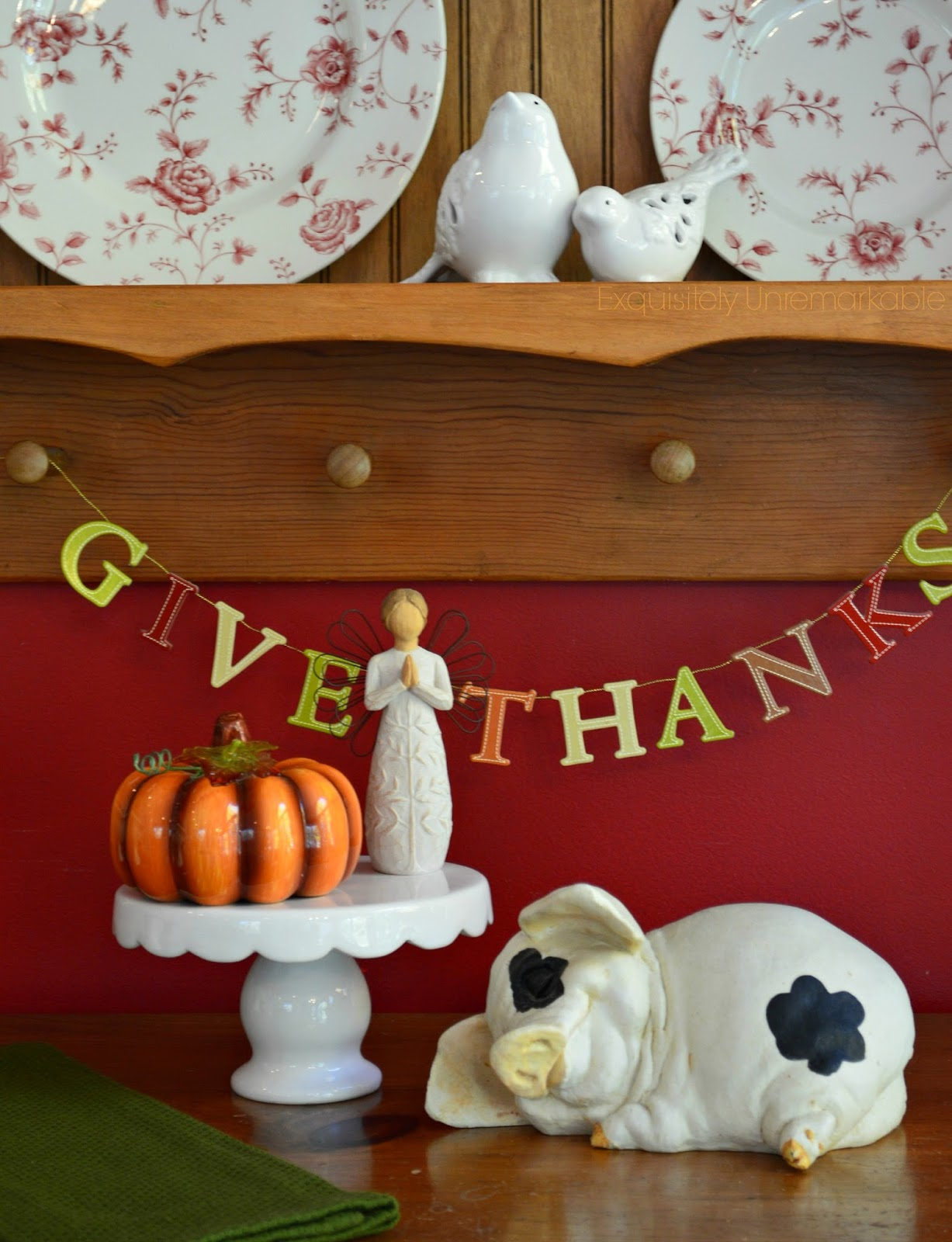 Give Thanks Letter Banner hung on a plate rack next to small statues of angel, pumpkin and sleeping piglet