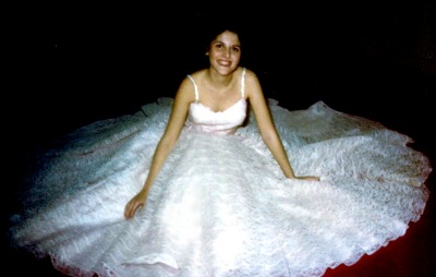 Young lady posed in floor with fluffy lace dress spread out around her