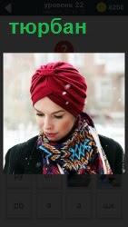 В зимнее время на девушке в пальто одет тюрбан красного цвета и цветной платок вокруг шеи