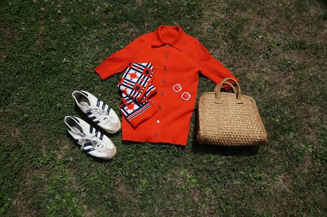 un polo orange en tricot , un foulard BBO , un sac en paille , des Adidas