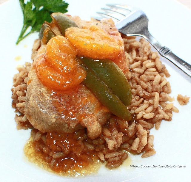 A thickened mandarin orange sauce with boneless pork over rice and peppers
