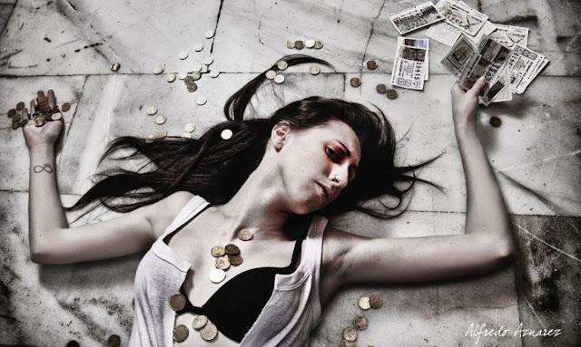 Mujer tirada al piso rodeada de monedas esparcidas