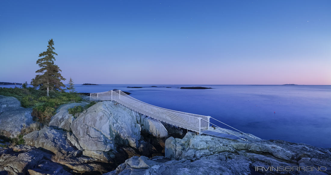 A bridge crosses a gap in the boulders as part of the hardscape design of an oceanview Southport Estate in Maine.