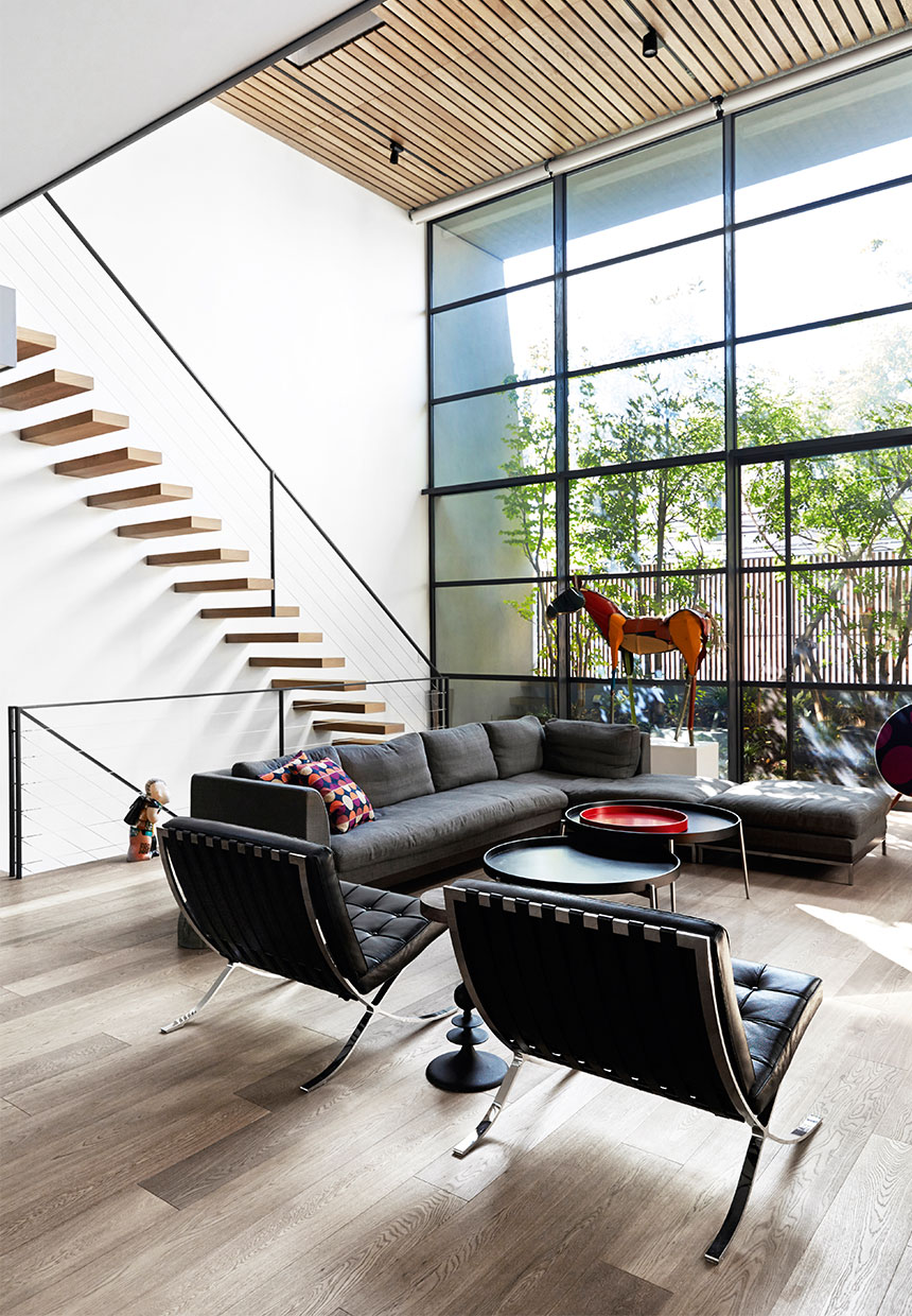 barcelona chairs, wood staircase, large window, horse statue