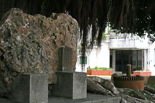 金武グスクの城門の石とサーターグルマの歯車の写真