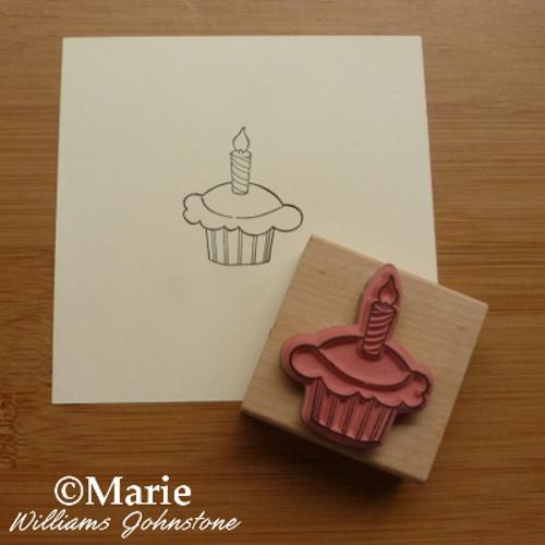 Black outline print of a cupcake rubber stamp design on paper
