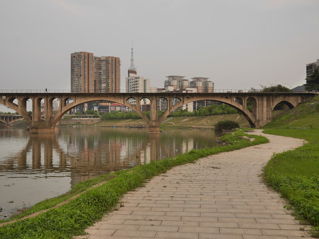 brick path alongside a river and a person walking on a bridge crossing the river