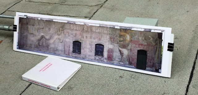 The Getty Conservation Institute's Monitoring Notebook and a visual of América Tropical on the roof of the Italian Museum at El Pueblo de Los Angeles National Monument, March 21, 2017 Photo: Shelly Kale; mural: © 2012 Artists Rights Society (ARS), New York/SOMAAP, Mexico City
