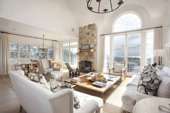 living room with french doors, neutral sofas and matching armchair with sea shell print accent pillows, a coffee table with a wooden top, fireplace with stone mantel, floor length curtains and a chandelier