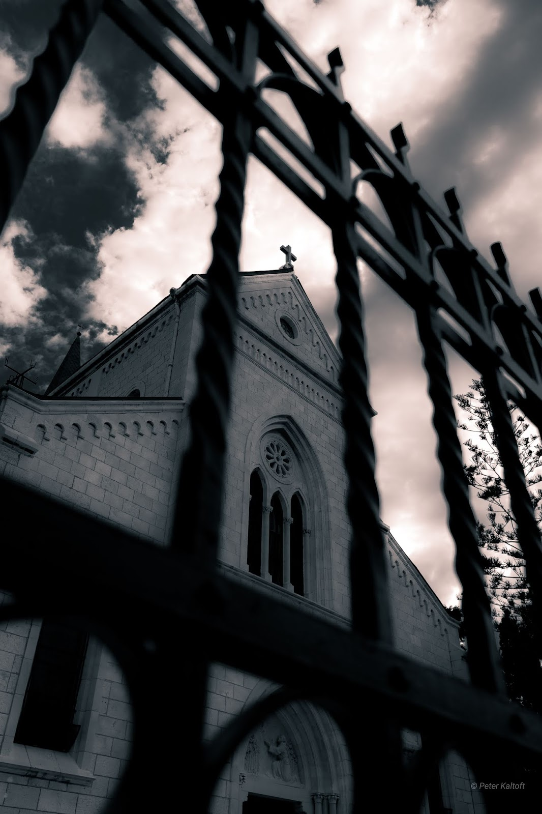 St. Anthony's Church seen through the bars in front of the church from a dramatic angle.