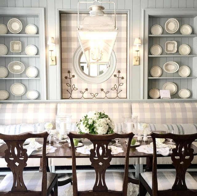Stunning built-in blue painted shelves with lace creamware plates and banquette