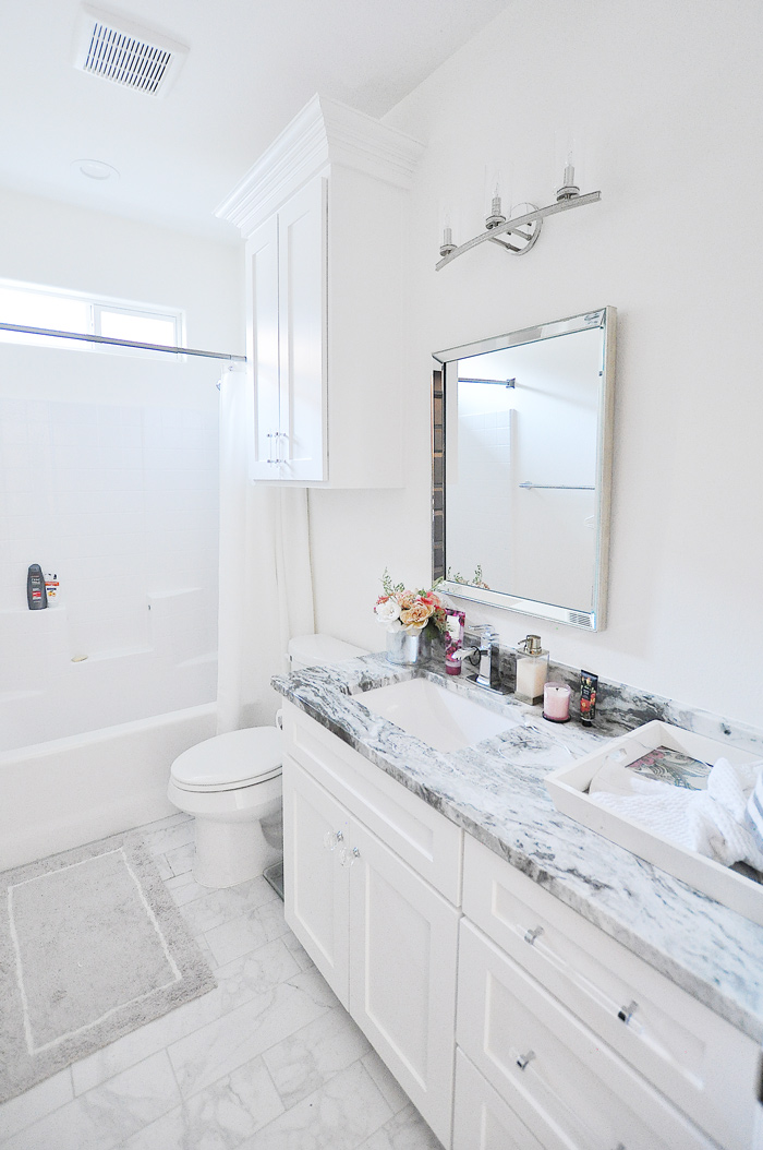 A crisp white guest bathroom with shaker cabinets, crystal lighting, lucite hardware and a marble tile floor with white walls.