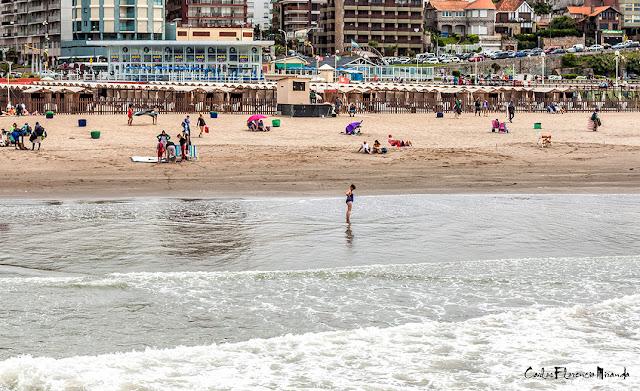 Foto una mujer sola con los pies en el mar y gente en la playa
