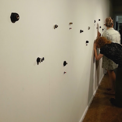 A woman peering into one of several small holes in an art gallery wall.