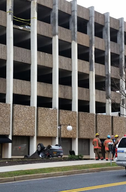 Woman survives with minor injuries as car falls from fourth floor of a story building (pics)