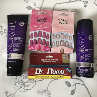 flatlay of pink stick on nails and norvell tan and dr numb