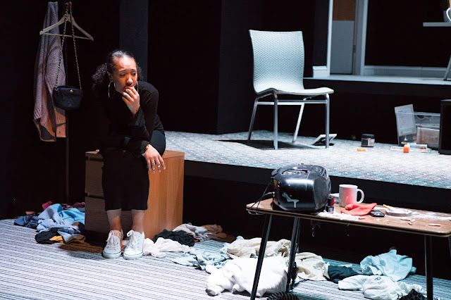 A young woman is sat on a set of drawers looking very worried in a dishevelled room.
