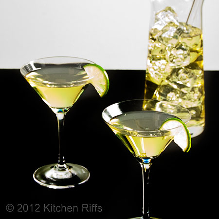 Gimlets in Cocktail Glasses with Lime Garnish, Mixing Beaker in Background