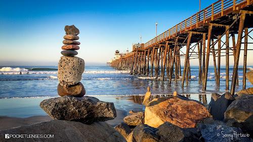 Pedras empilhadas em uma praia, com o mar e um pier ao fundo (créditos no final do post)
