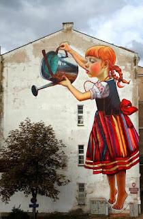 Natalia Rak e seu gigantesco grafite em Bialystok, Polônia. A foto mostra um gigantesco grafite na parede lateral de um prédio. O grafite à direita é de uma garota ruiva com trancinhas e traje típico polonês: Vestido regata com corpete preto, saia listrada em tons de vermelho, azul, amarelo e branco. O vestido tem um grande laço vermelho na cintura e está sobre uma camisa branca de mangas curtas bufantes com bordados. A garota parece flutuar, está descalça, na ponta dos pés regando uma árvore natural à esquerda, junto à parede do prédio.