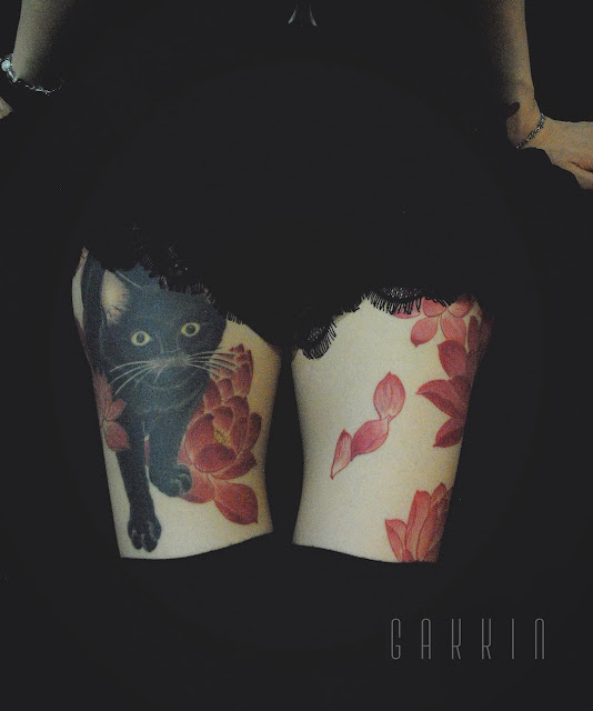 a cute tattoo made on a girl's thighs, surrounded by some simple red flowers