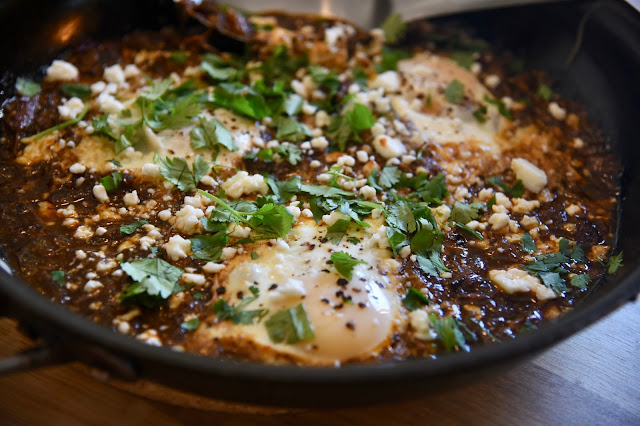 chipotle barbacoa in a skillet, topped with eggs, cotija cheese and cilantro