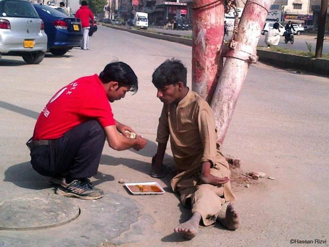A waiter at a restaurant buys food and feeds disabled beggar with his own hands.