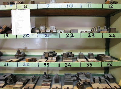 Pieces of metal arranged on numbered shelves.