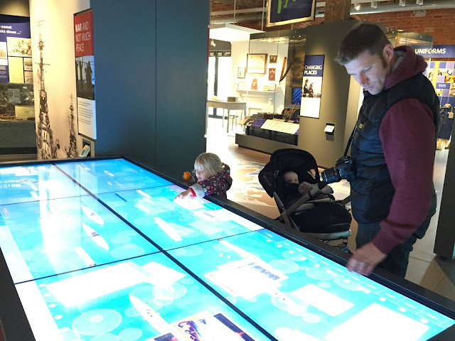 Mr Tin Box and Tot looking at an interactive museum display