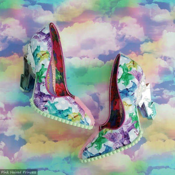 pair of shoes with unicorn printed uppers and lightning bolt heels on cloud background